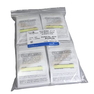 Clear plastic bag for fecal collection, 3 inches x 3 inches with wooden spoon on display card with black text and space to write information